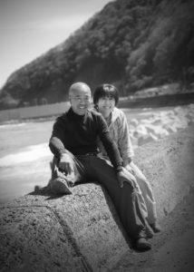 漁師夫妻の記念写真。海岸をバックに。(モノクローム写真)