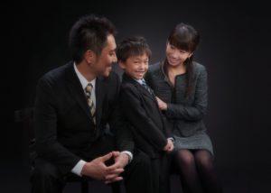 スーツでおすましの男の子とそれを見守るご夫婦の家族写真です