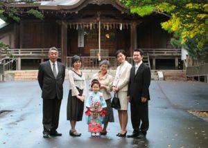 七五三記念の女の子を囲んで写る親族。神社本殿前で撮影しています。