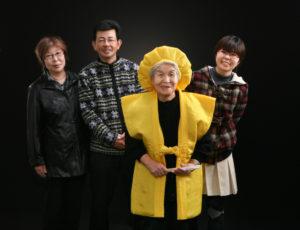 米寿祝。黄色のちゃんちゃんこの<母と祖母>を囲む子ども夫婦とお孫さんの記念写真。