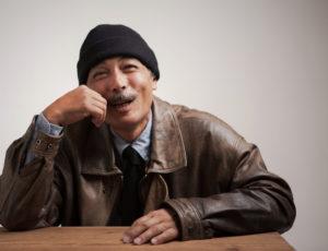 富士フィルム営業写真コンテスト入賞作。男性が机に肘をついて、笑っているポートレート写真