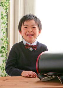 真新しいランドセルを横において笑顔がいいねえ。入学記念フォト。