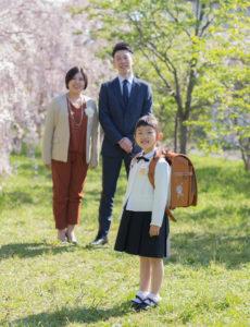 ランドセルをしょった娘の入学をにこやかに眺める父と母。桜の季節の一枚です。