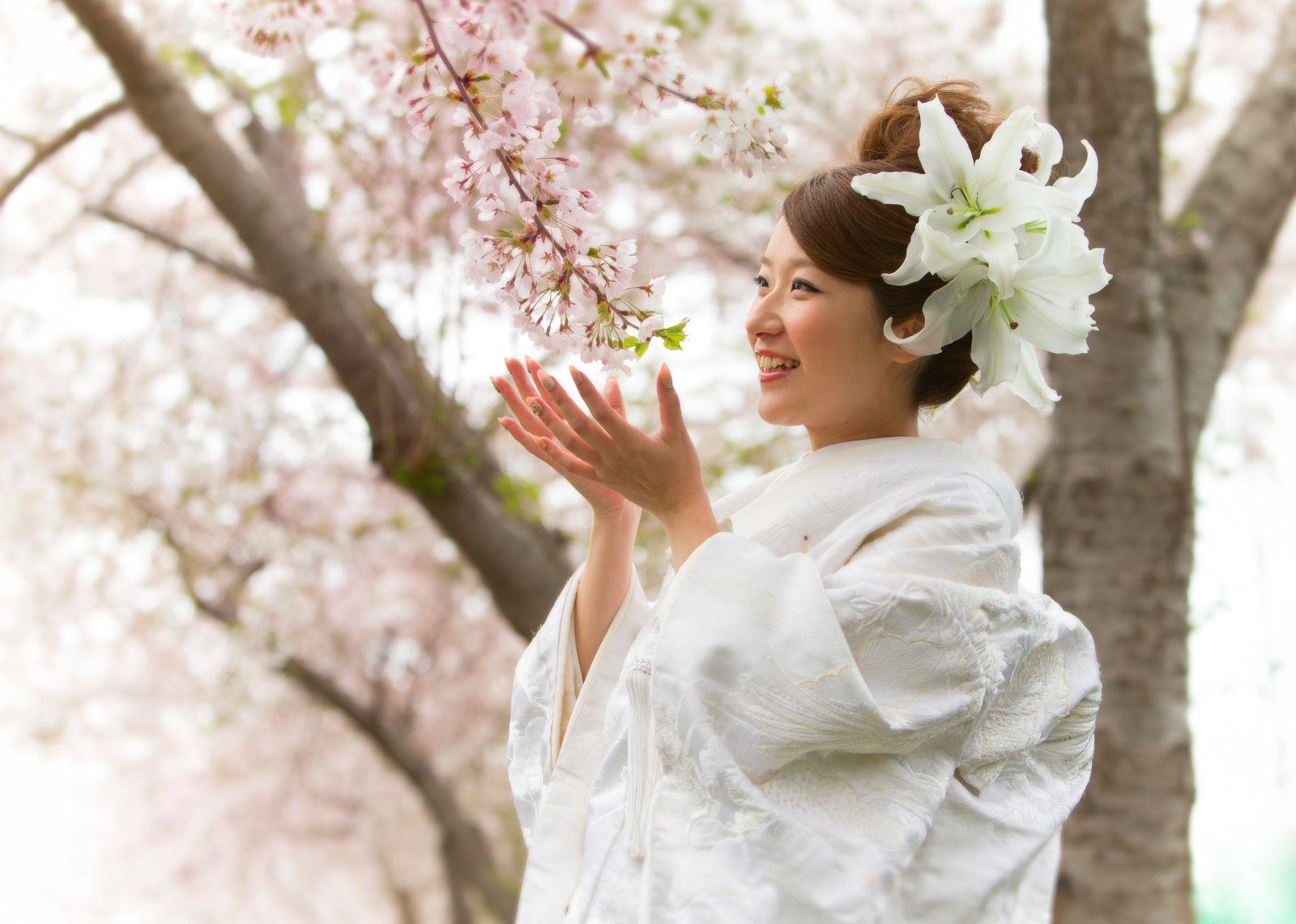 桜の花を手のひらでつつむように立つ花嫁。結婚写真。和装